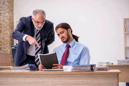 Old male boss and young employee working in the office Stock fotó