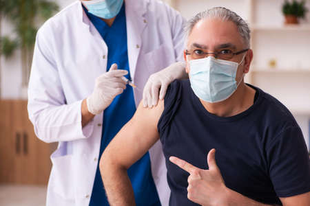 Old man visiting young doctor in vaccination concept Standard-Bild