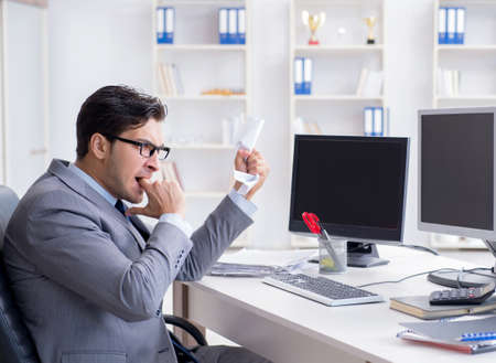 Businessman sitting in front of many screens Stock Photo