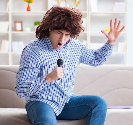 Funny man singing songs in karaoke at home Banque d'images