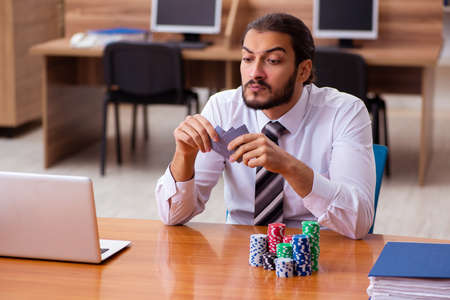 Young male employee in gambling concept