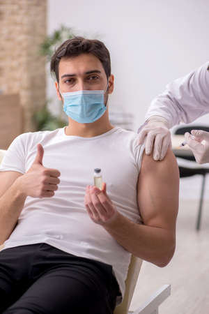 Young male patient visiting old male doctor in vaccination conce