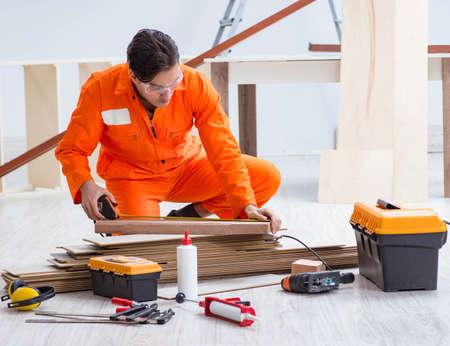 Contractor working on laminate wooden floor Foto de archivo