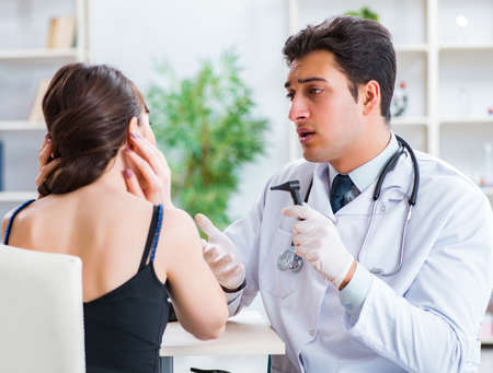 Doctor checking patients ear during medical examination Imagens