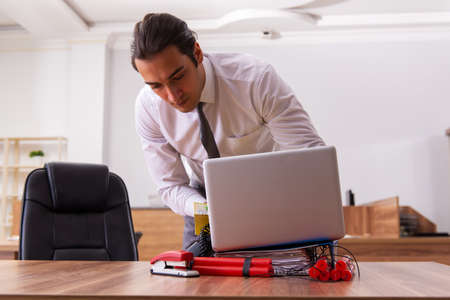 Young male employee with dynamite in the office