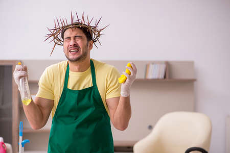 Young male contractor wearing prickly wreath on head cleaning th Stock fotó