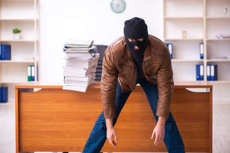 Young man in balaclava stealing information from the office Imagens