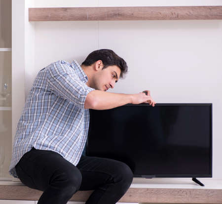 Man repairing broken tv at home Stockfoto