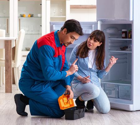 Man repairing fridge with customer Stockfoto