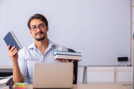 Young male teacher in front of whiteboard