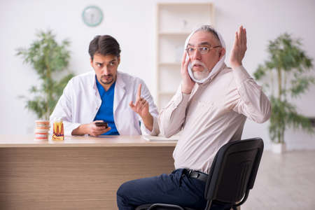 Old male patient visiting young male doctor dentist