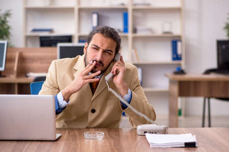 Ill cigarette addicted male employee working in the office Stock Photo