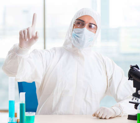Young chemist pressing virtual buttons in lab Banco de Imagens