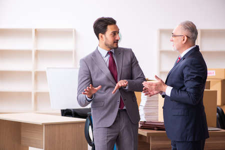 Young realtor and old boss in relocation concept