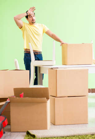 Young handsome man moving in to new house with boxes Stockfoto