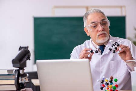 Old male teacher chemist in the classroom