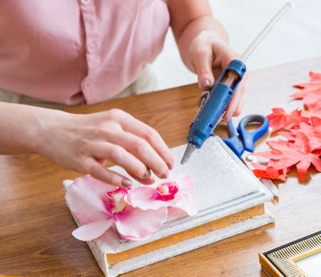 Woman decorating picture frame in scrapbooking concept Standard-Bild