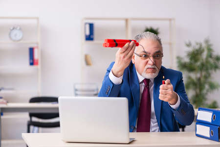 Old male employee with dynamite in the office