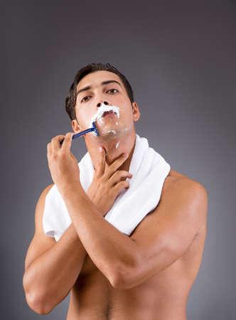 Handsome man shaving against dark background Stock Photo