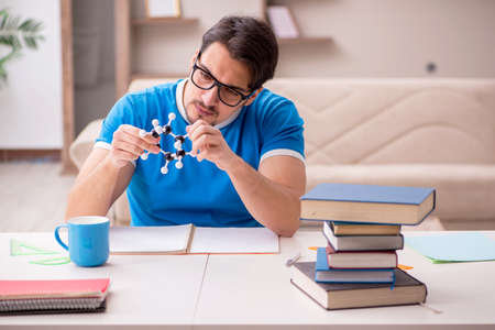Young male student physicist studying molecular model