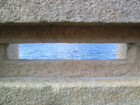 Granite window in old fortification with sea panorama, Caprera Island, Sardinia, Italy