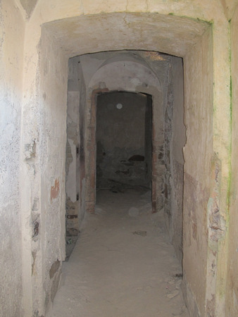 Tunnel doors in vintage old ruined building with damaged plaster walls