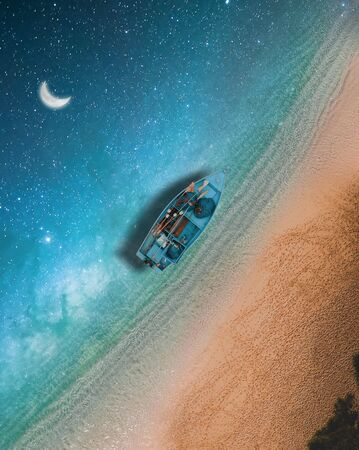 Surreal perspective top view of a sandy beach with night sky instead of sea, starry night with half moon, a fishing boat floats in this imaginary scene
