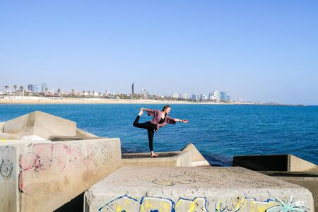 A girl doing some yoga positions and routines in different spots in Barcelona. Foto de archivo