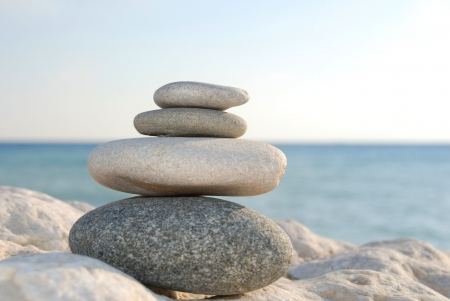 four stones lying upon another in front of the ocean Stock Photo - 16077888