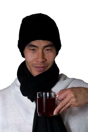 asian man in winter clothes holds an glas in his hand filled with punch or red tea Stock Photo - 16134286
