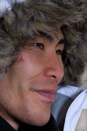 man in outline who looks asian or inuit with coat above his head photo