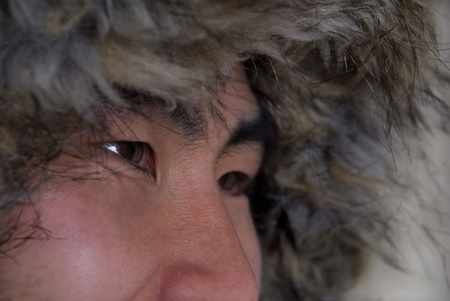 closeup of asian or inuit looking man with coat above his head, in outline photo