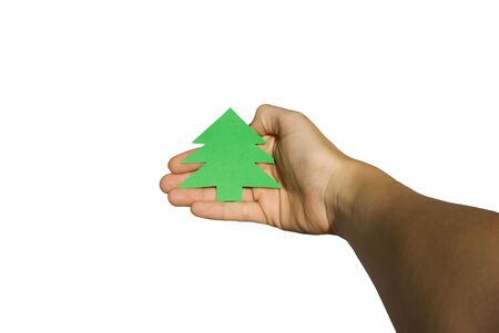 hand which holds a green sign in form of a christmas tree with copy space on white photo