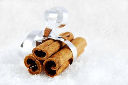 sociability: three cinnamon sticks as a present lying in the snow Stock Photo