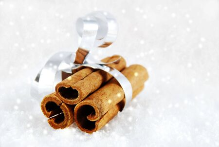 sociability: cinnamon sticks as a present in the snow with white snowflakes Stock Photo