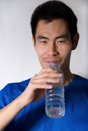 dynamically: asian man drinks water out of a small water bottle
