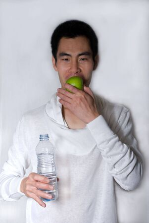 healthy looking asian man bits in an apple and holds a small bottle of water in his hand photo