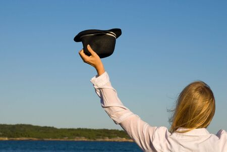 blond person waving goodbye or welcome with hat in front of the sea photo
