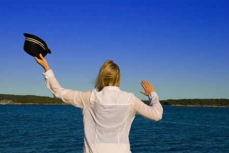 woman in front of the sea, waving to say goodbye photo