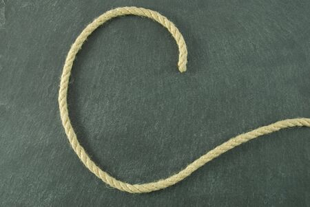 a C of rope lying on a slate table, symbolizing education and writing Stock Photo - 16326666