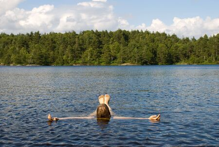 healthfulness: a person lying in the water for recreation i a natural environment Stock Photo