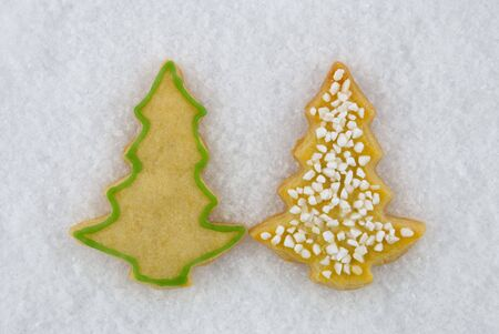 two christmas tree cookies lying next to each other in the snow photo