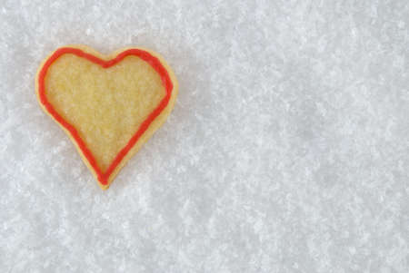 a heart christmas cookie lying in the snow photo