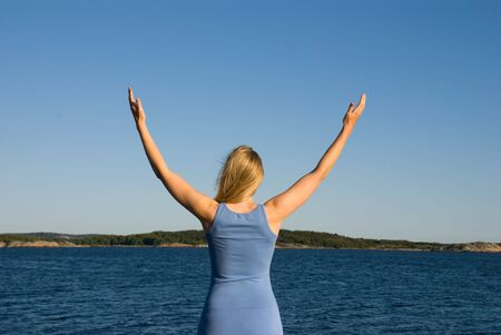 a woman standing at the sea, relaxing, meditating, salutating, preaching or praying Stock Photo - 16570074