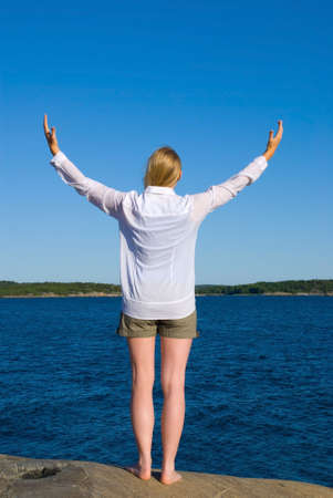 a woman standing in front of the ocean with arms wide open Stock Photo - 16570069