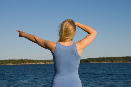 a young european looking woman in blue cloth standing at the coast of the ocean shows something Stock Photo - 16808707