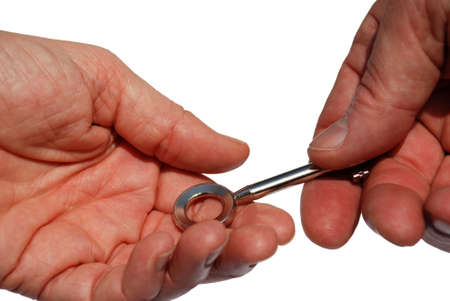 consign: closeup of two hands reaching a key