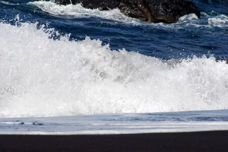 a breaking wave at the waterside with black sand Stock Photo - 17313744