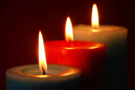 coziness: three lighted candels in a row with dark red background