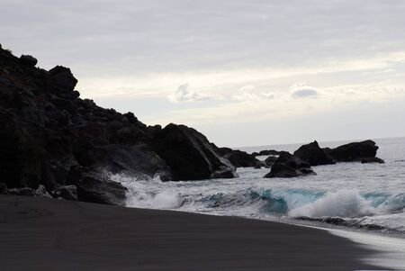 reclusion: black sand and black lava stones at sea seaside, black beach with waves